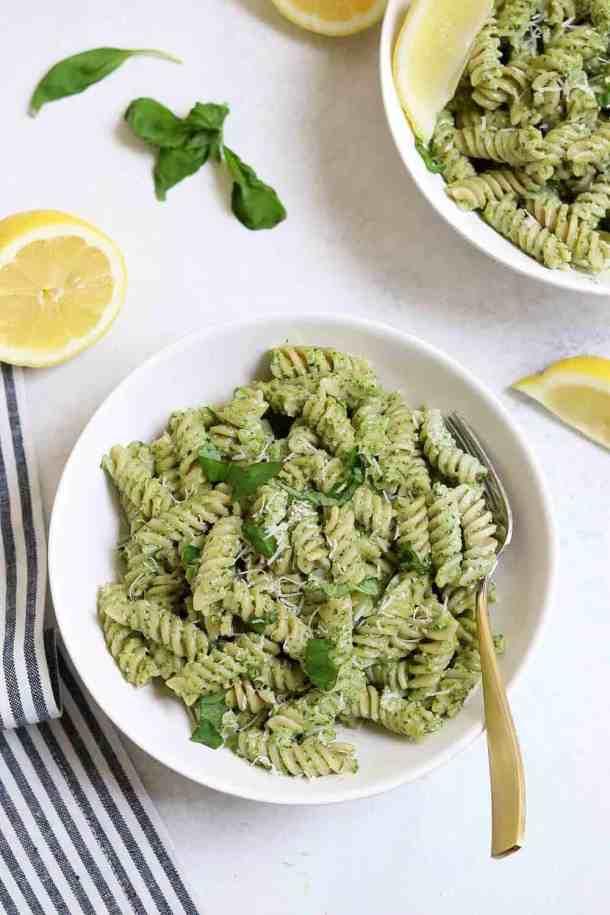 Vegan pesto pasta with fresh basil in a white bowl.