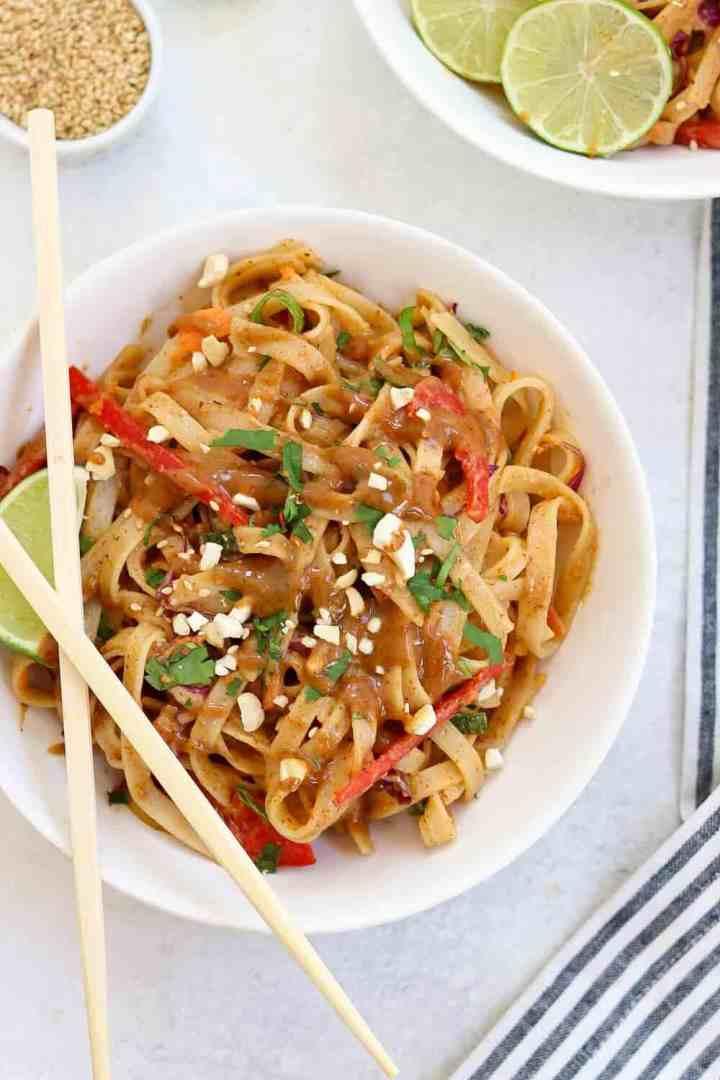 White bowl with noodles and sauce on top with tan chopsticks on the side.