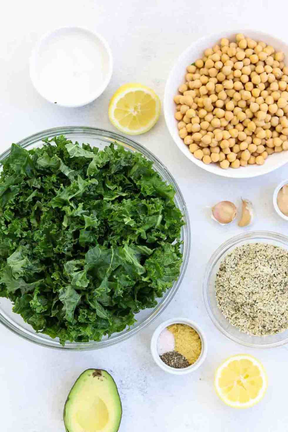 Ingredients for the kale caesar salad arranged in bowls with a grey backdrop.