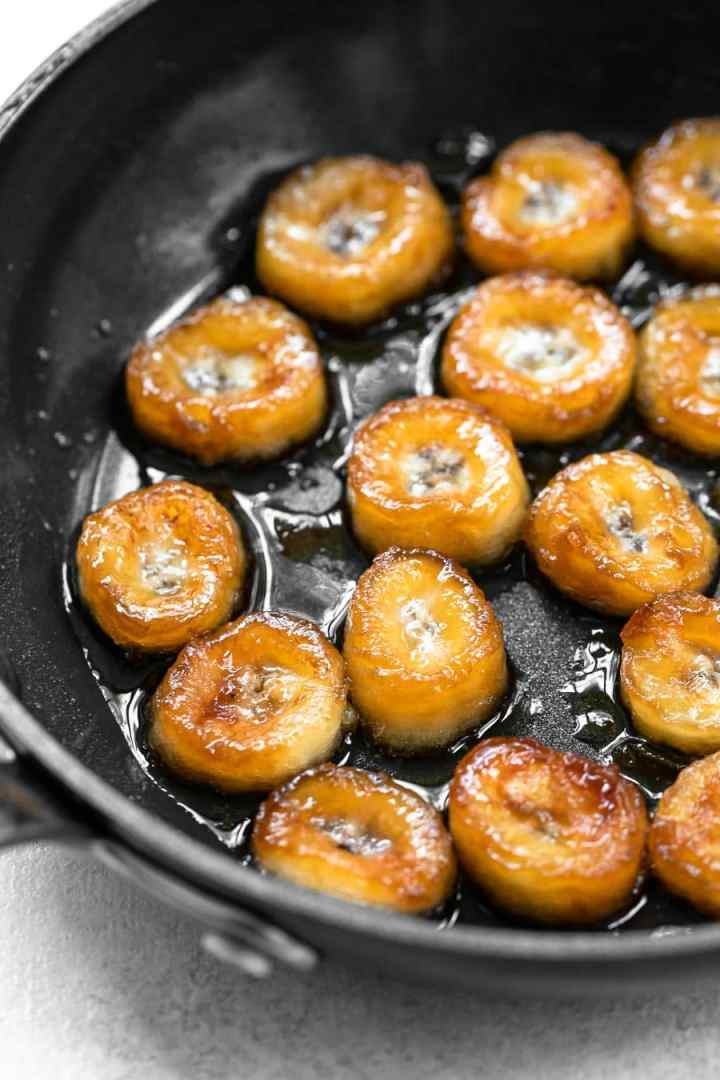 Black skillet with a bunch of golden brown caramelized bananas.