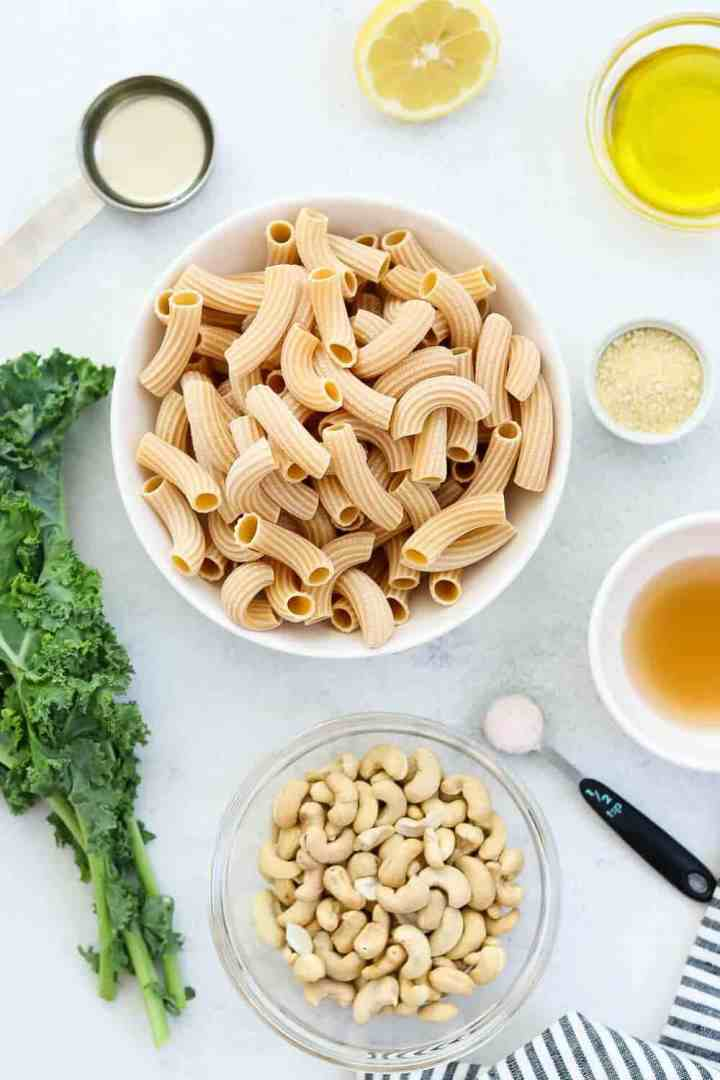 Ingredients for this pasta dish arranged on a white backdrop.