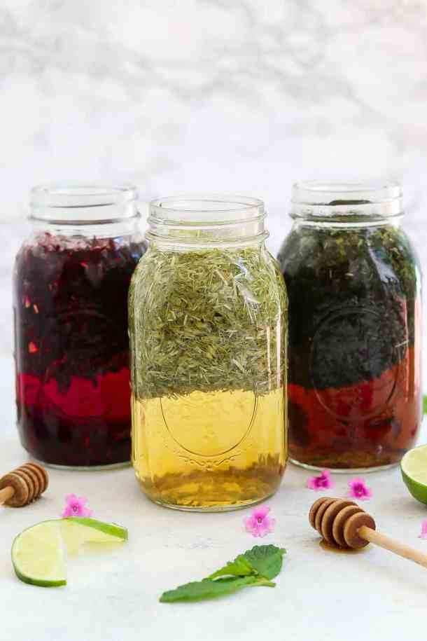 Three jars of herbal infusion arranged on a white backdrop.
