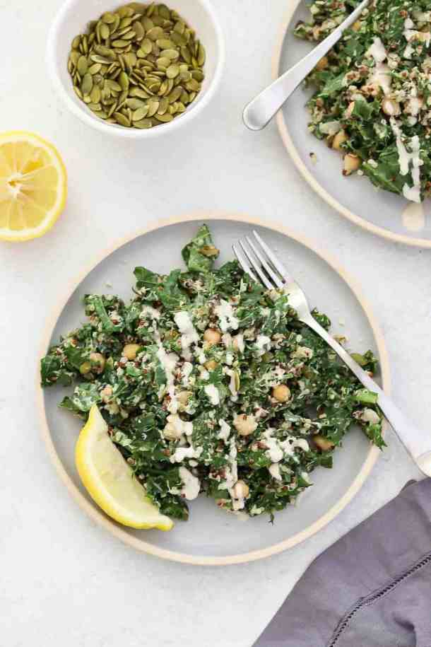 Overhead shot of kale and quinoa salad on blue plate with lemon tahini dressing on top.