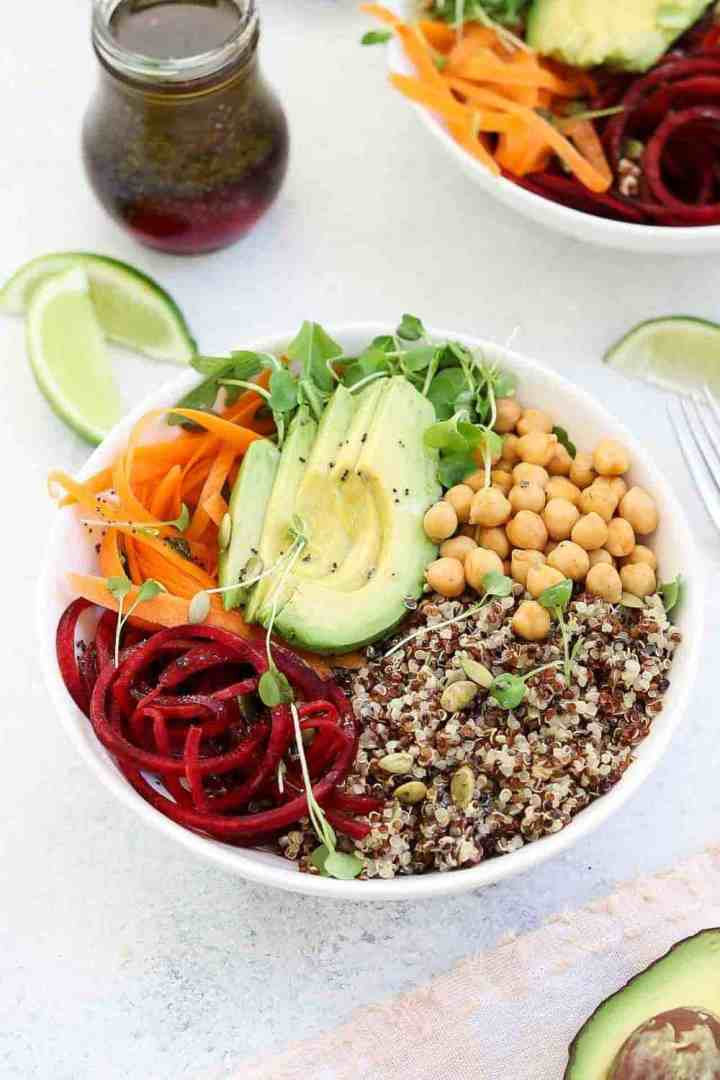 up close of quinoa buddha bowl with avocado in the center.