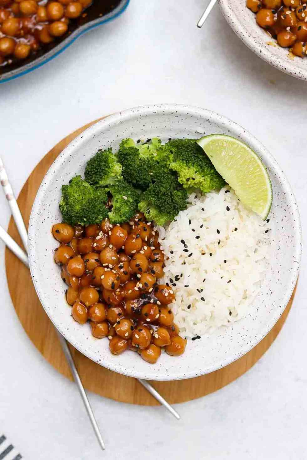 Speckled bowl with sesame chickpeas, white rice, broccoli, and a lime wedge.