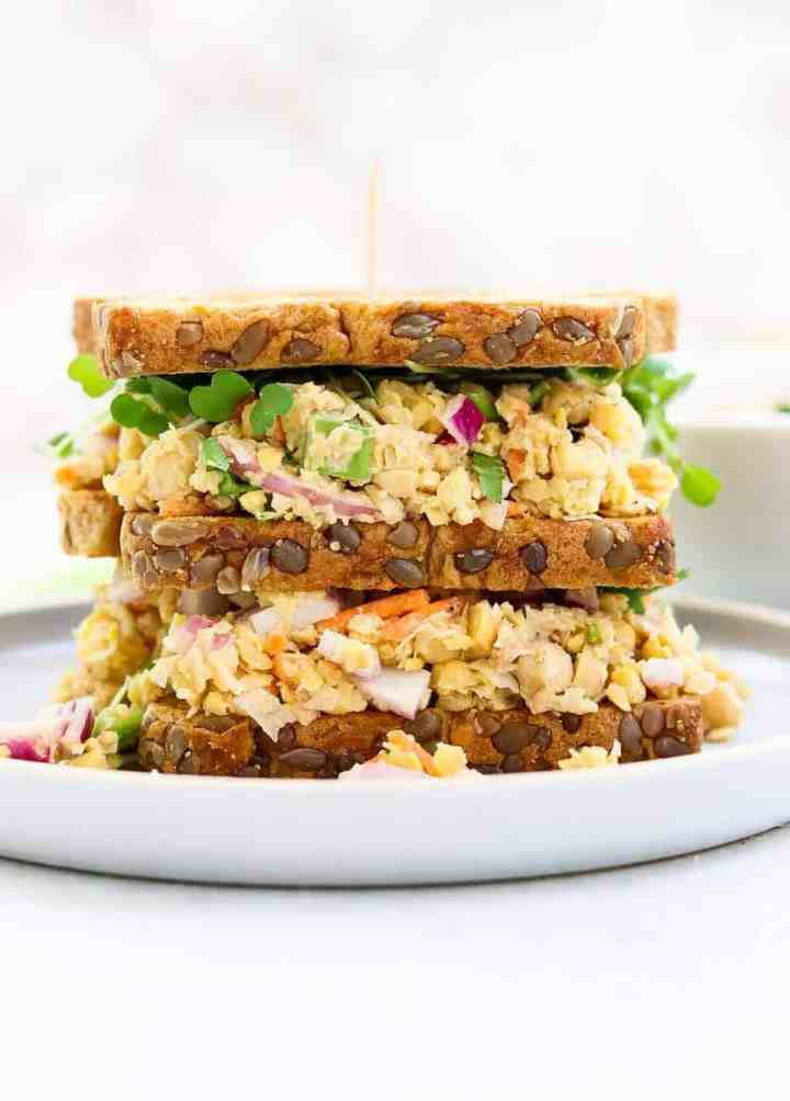 Vegan tuna salad sandwich with three pieces of bread on a small blue plate.