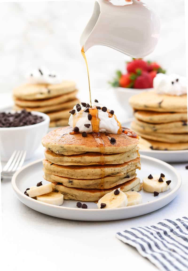 Chocolate chip pancakes with whipped cream on top and maple syrup being poured over.