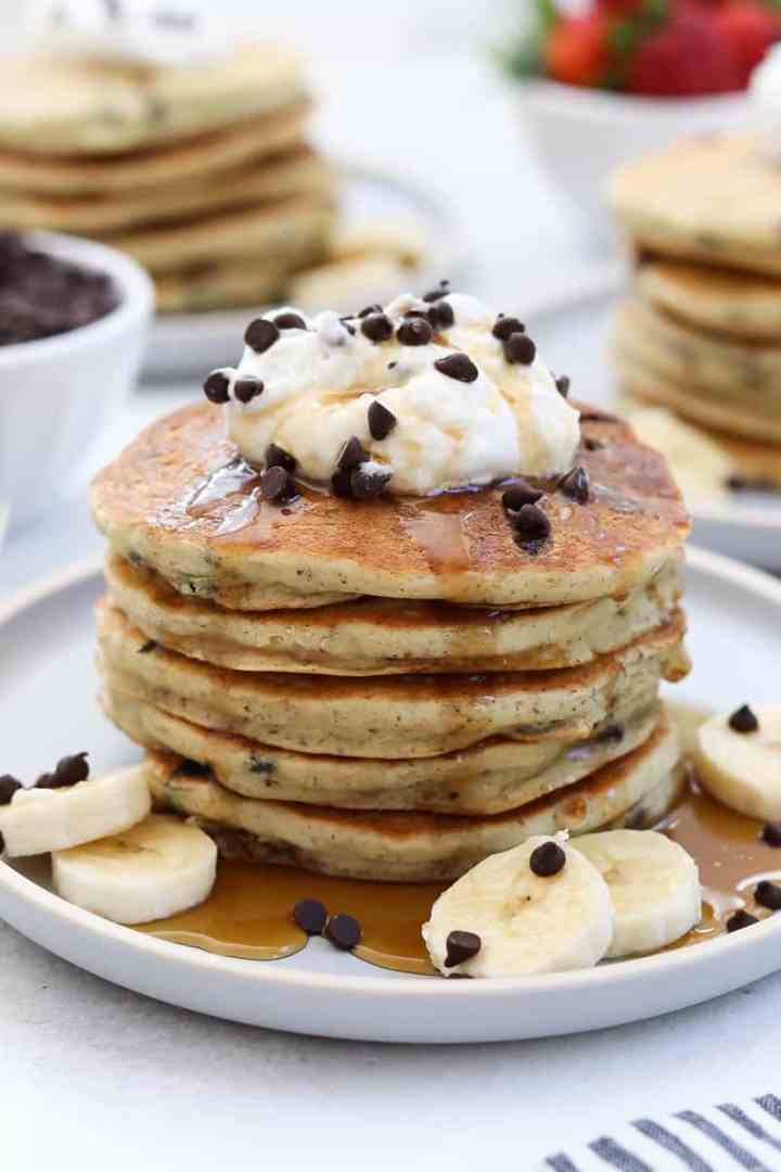Pancakes with whipped cream, banana and maple syrup on top.