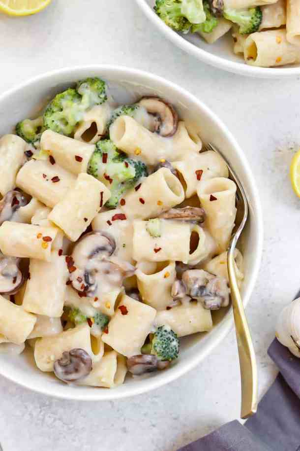 Up close of vegan cream sauce with pasta and vegetables.