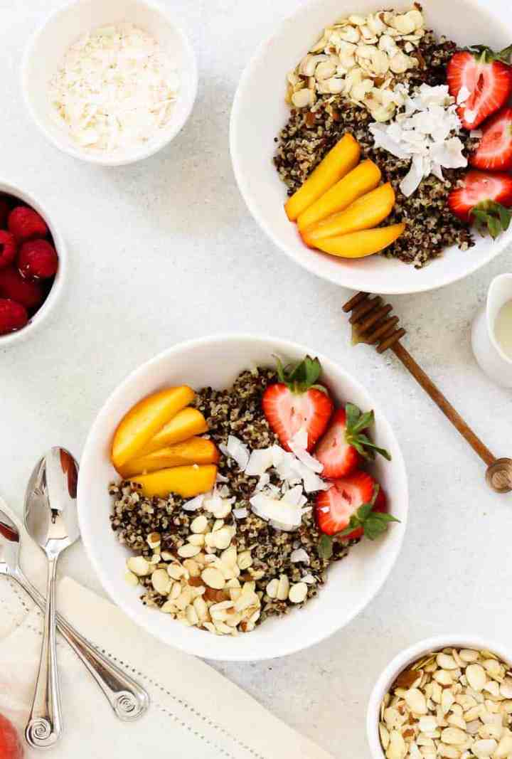 Quinoa breakfast bowl with peaches, strawberries and almonds in two white bowls.