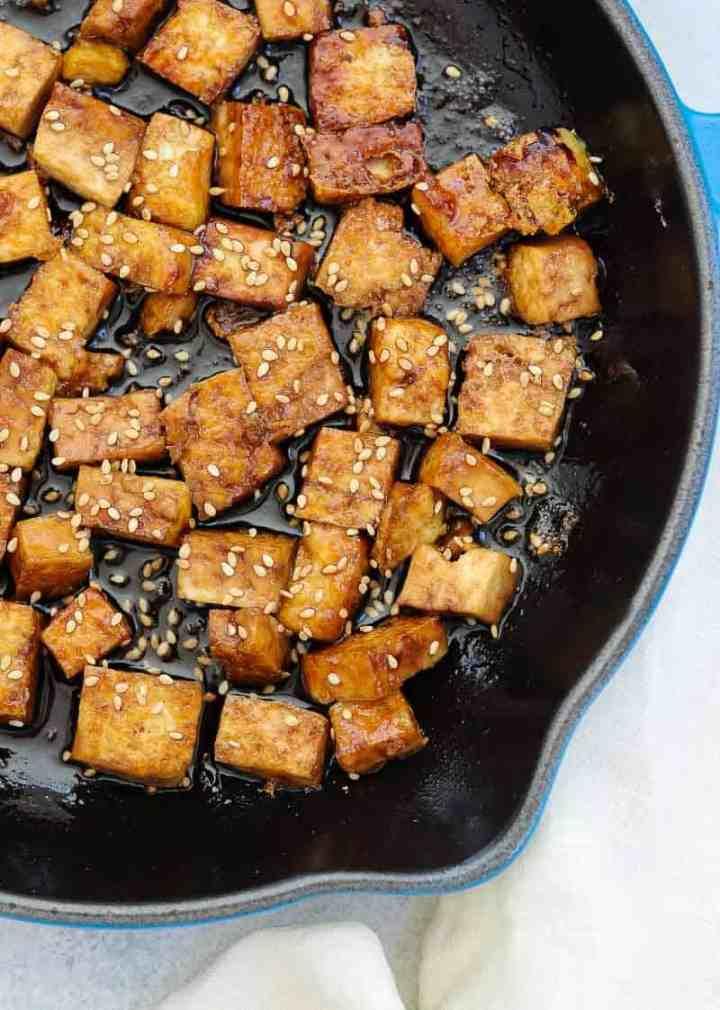 Sesame tofu in a black skillet with sesame seeds sprinkled on top.