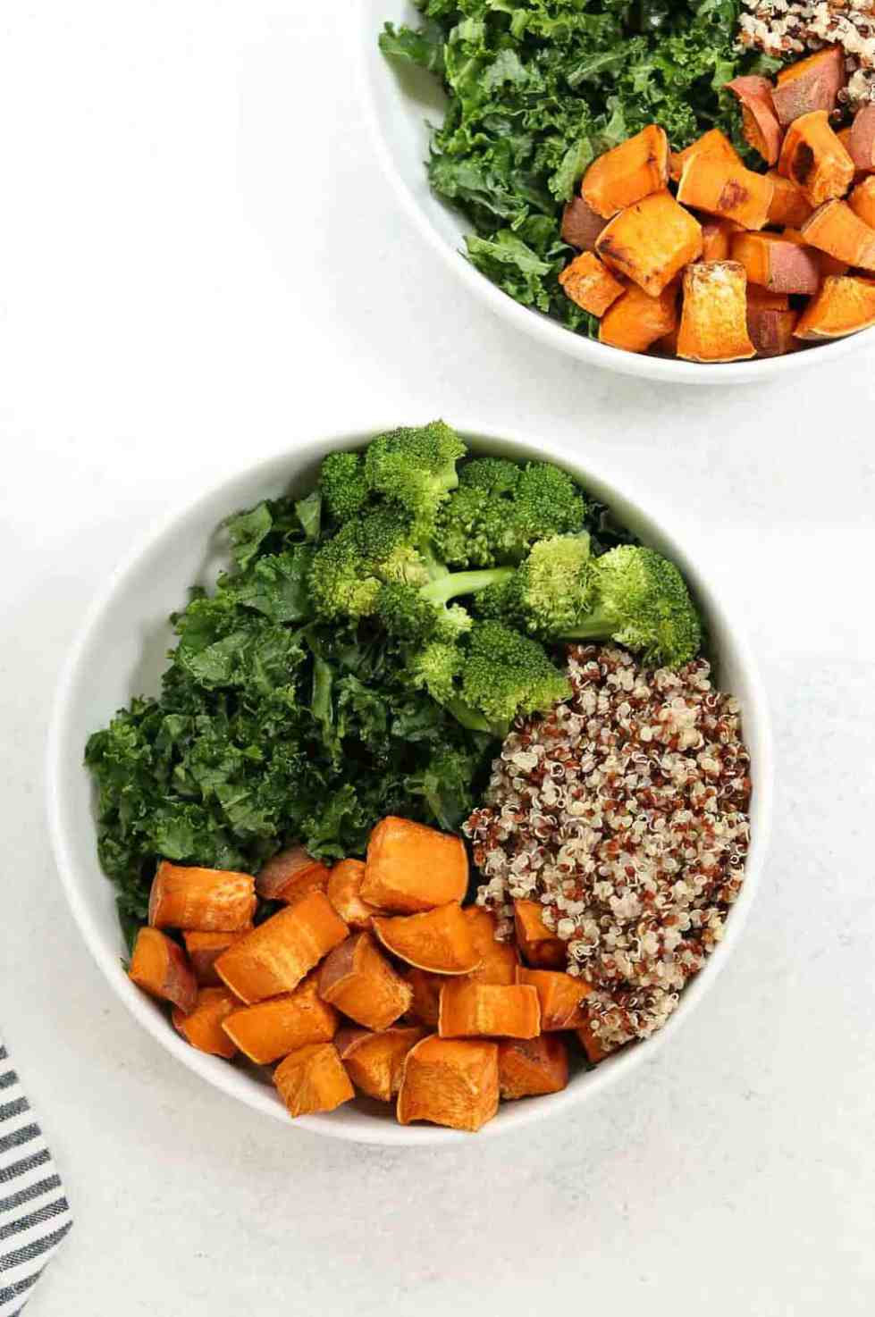 kale, sweet potato, broccoli and quinoa in two white bowls.