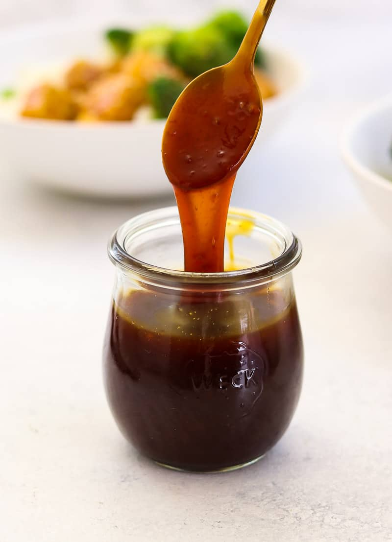 Teriyaki sauce in a small glass jar with a spoon showing the sticky sauce.