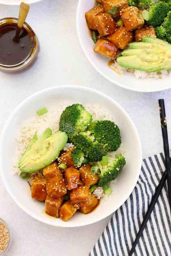 Two teriyaki tofu bowls with broccoli and avocado with sesame seeds on top.