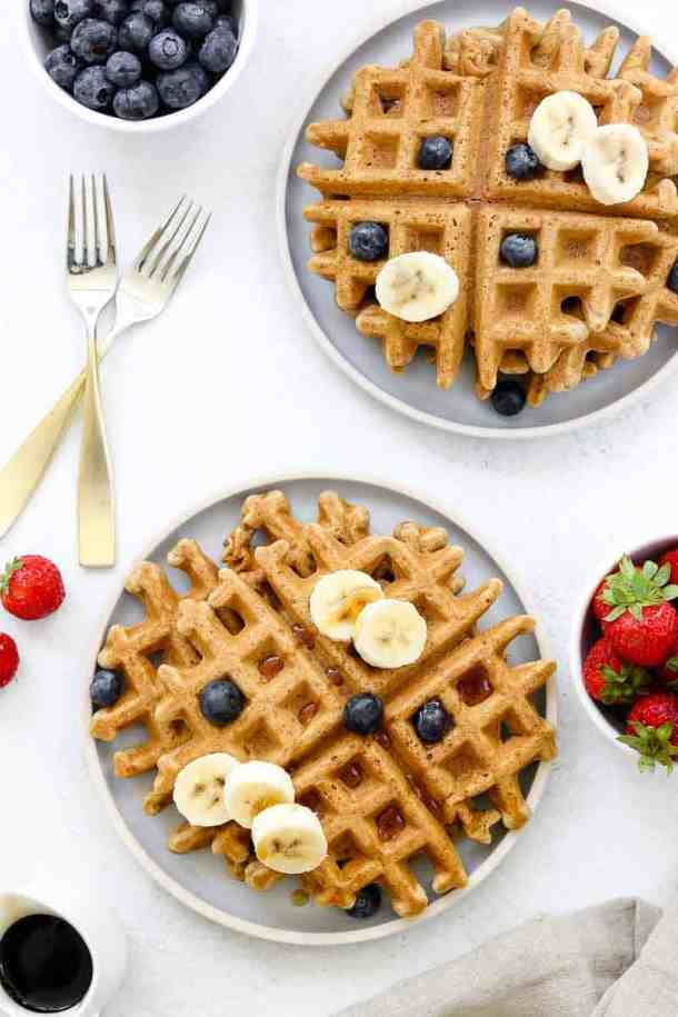 Gluten free waffle recipe on blue plates with berries.