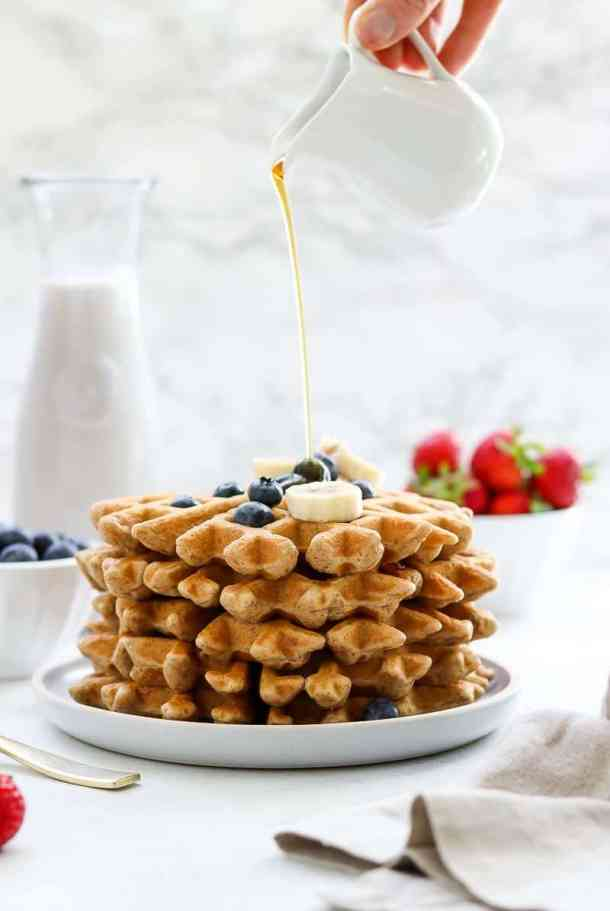 Gluten free waffles stacked on plate with maple syrup.