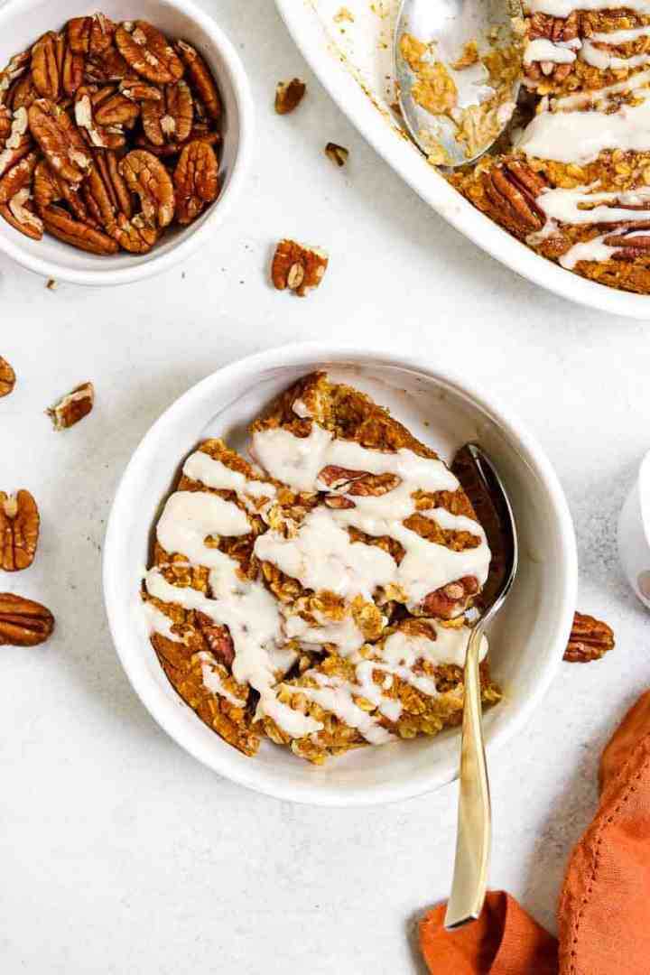 White bowl with pumpkin oatmeal and cream cheese glaze.