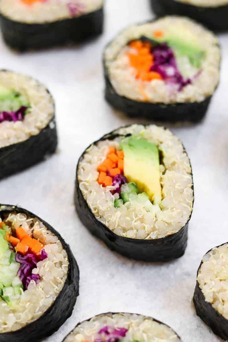 Finished sushi arranged on a grey backdrop.