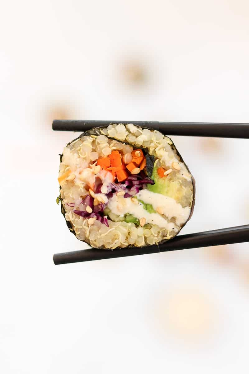 Chopsticks holding up a piece of quinoa sushi with miso dressing.
