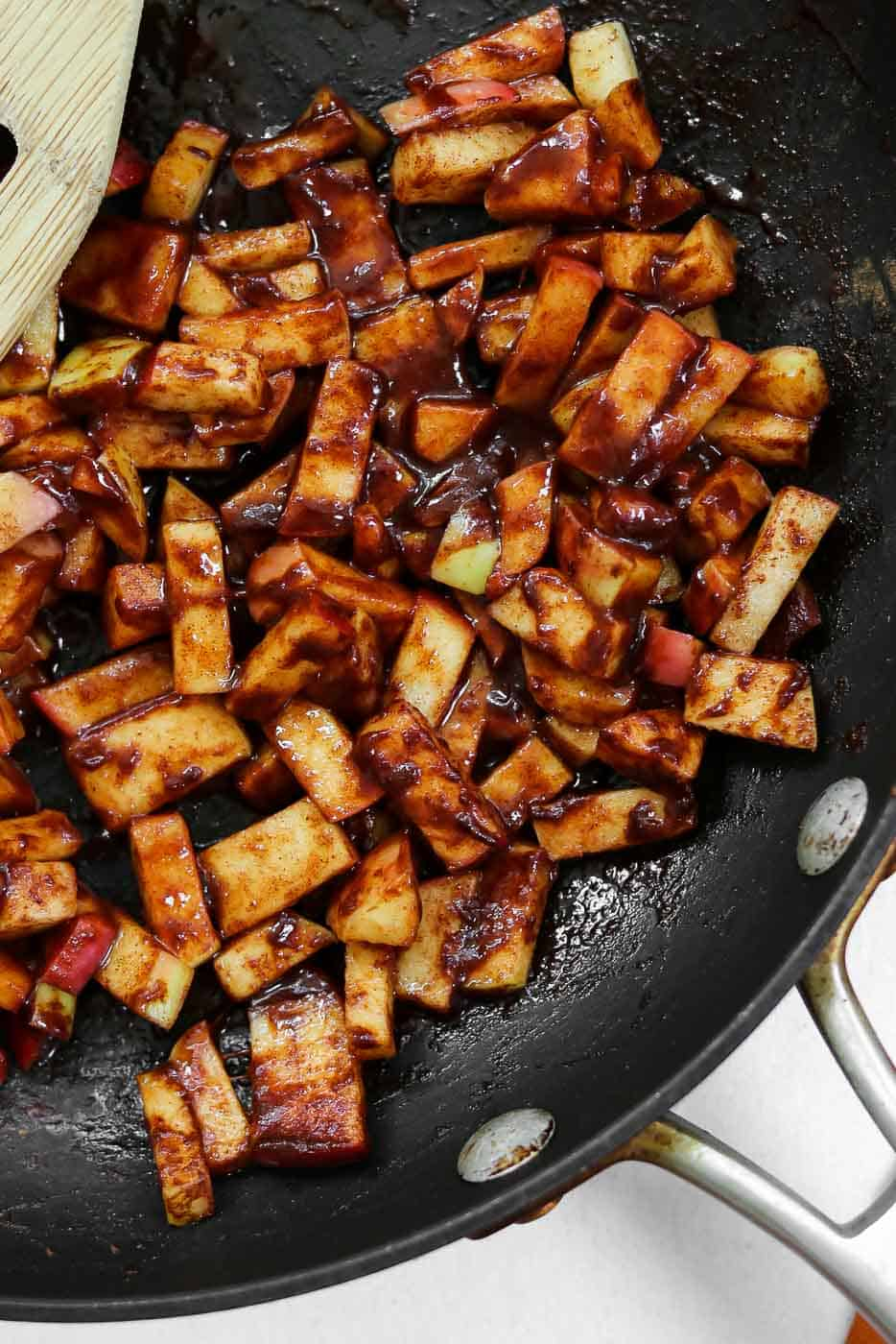 Chopped cinnamon apples in a black pan.
