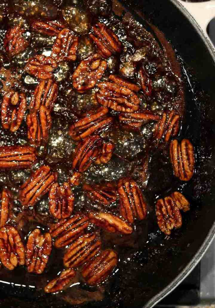 Pecans in a black pan getting candied.