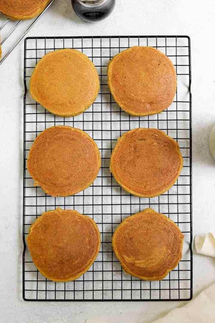 Six pancakes on a black cooling rack.