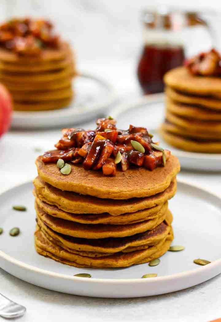 Pancakes stacked on a plate with apples and pumpkin seeds.
