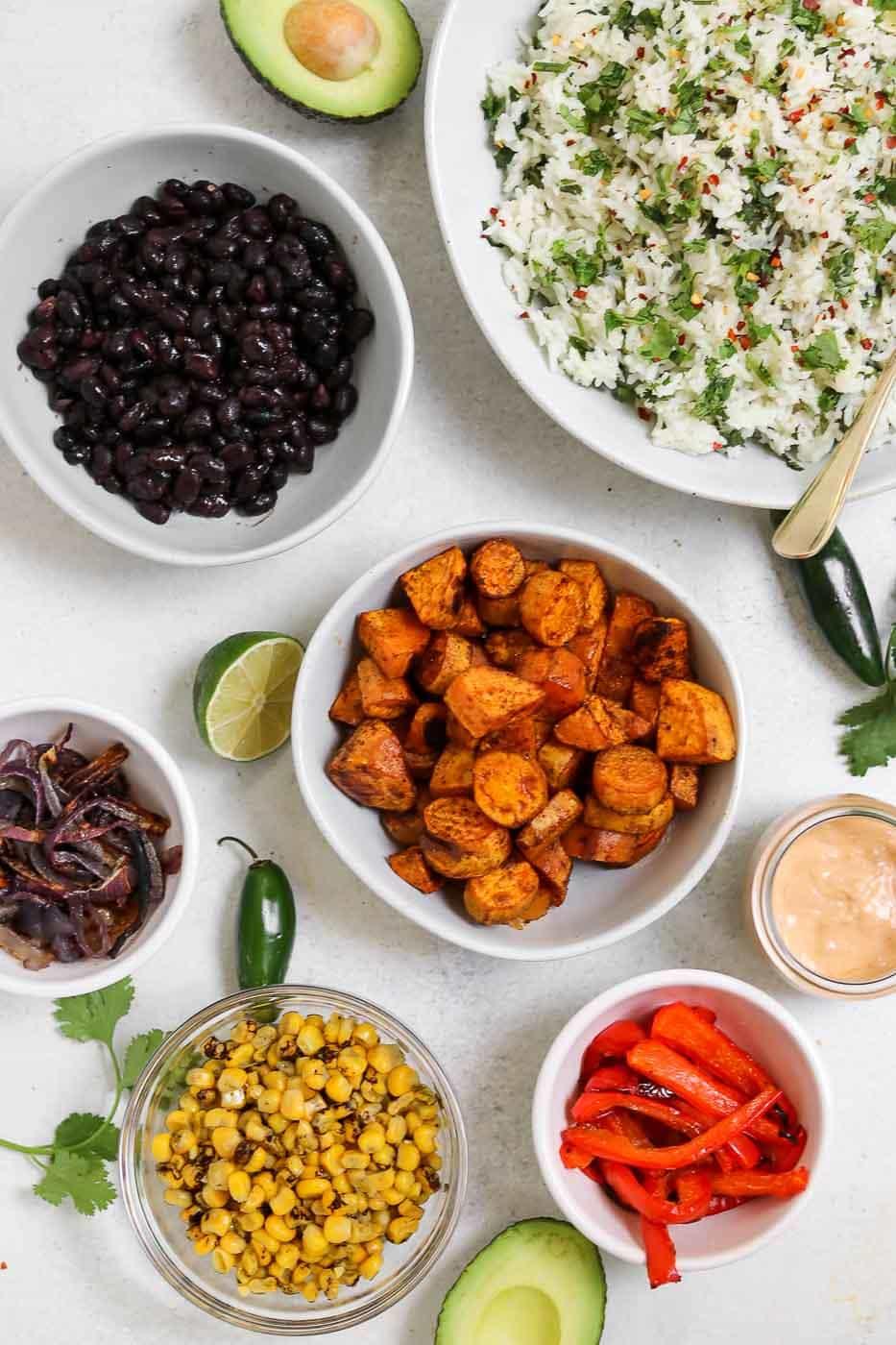 Ingredients for the vegan burrito bowl recipe in white bowls.