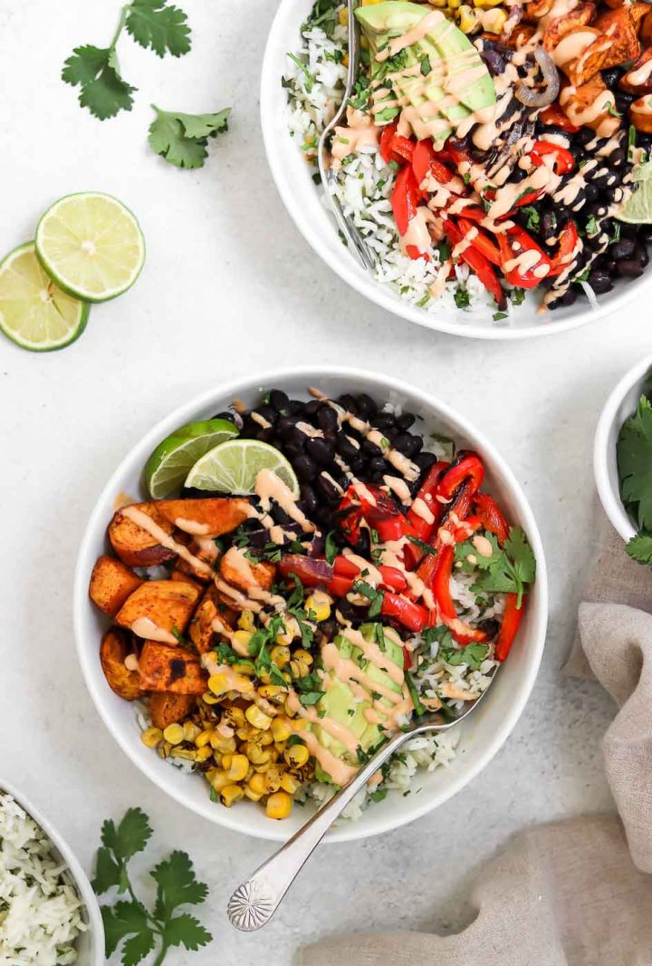Two vegan burrito bowls with veggies and fresh cilantro.