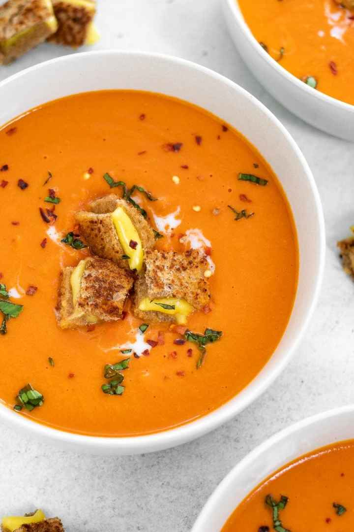 Up close image of soup with grilled cheese croutons.