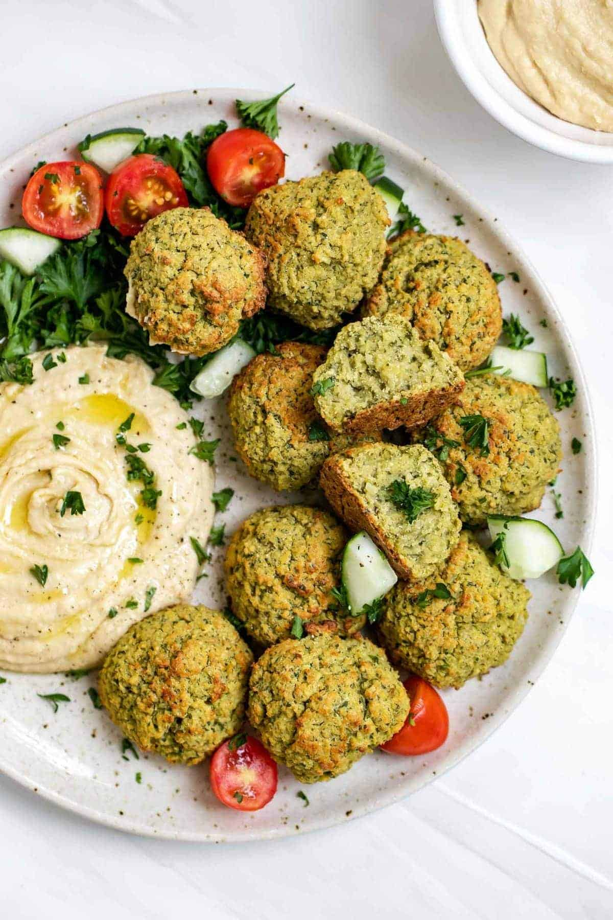 Vegan baked falafel with chickpeas on a plate with hummus.
