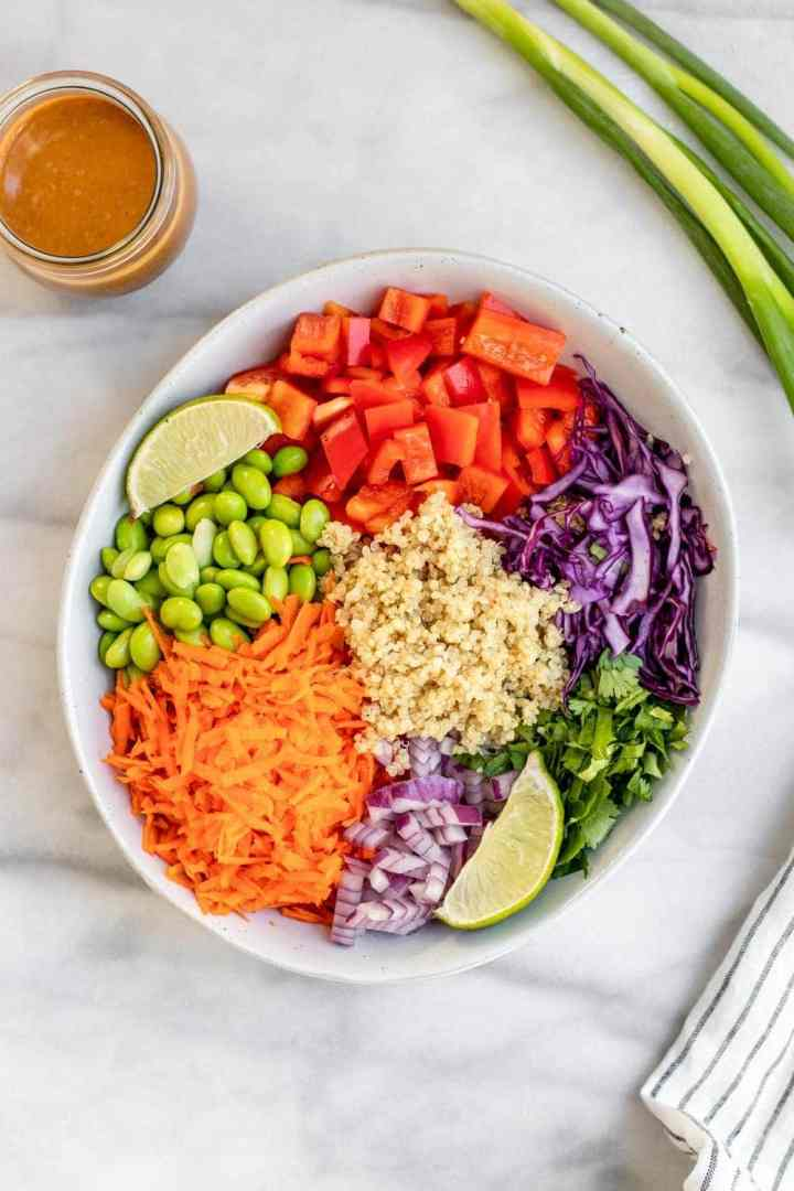 Salad arranged in a bowl with veggies on the side.