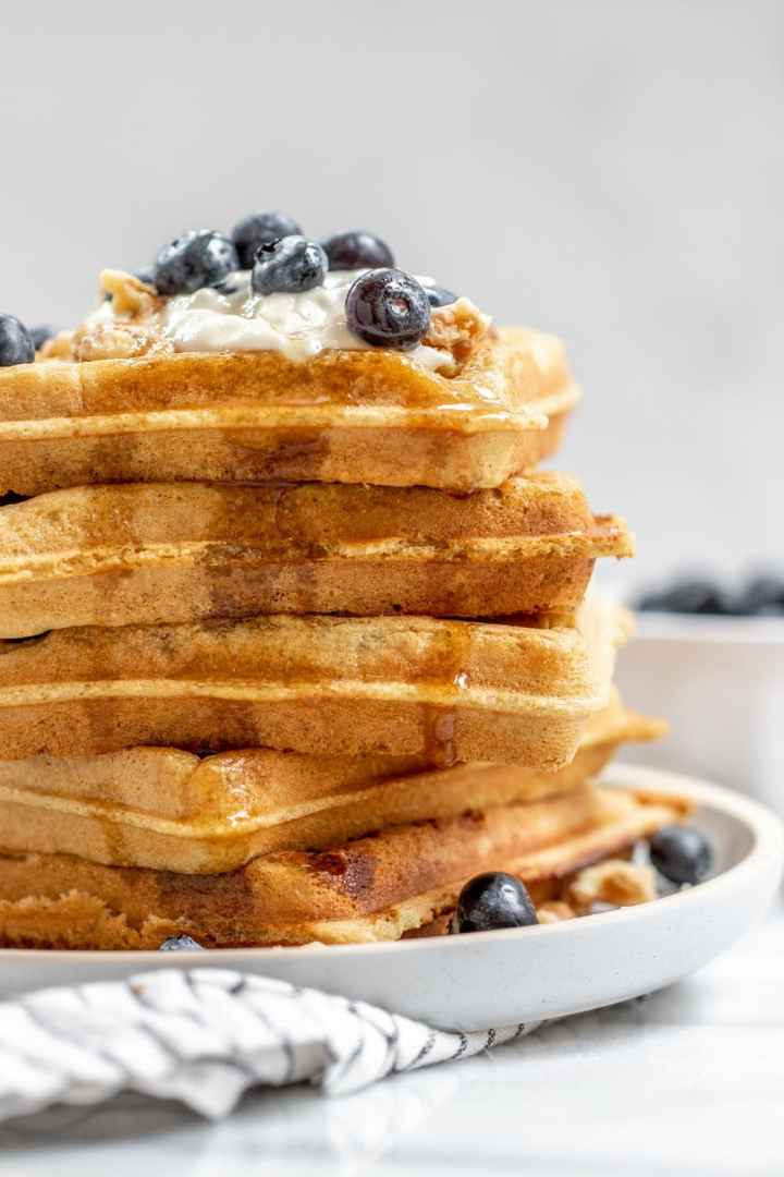 Tall stack of almond flour waffles with berries on top.