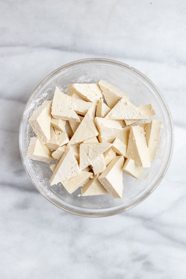 Cubed tofu in a small glass bowl.