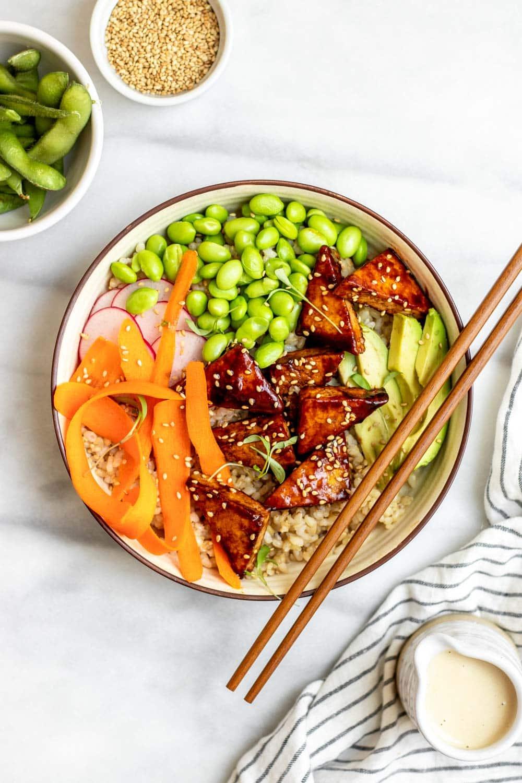 Vegan sushi bowl with sesame tofu and chopsticks on the side.