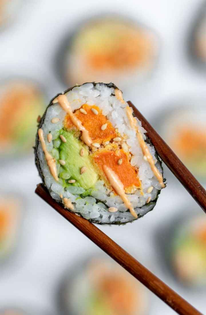 Chopsticks holding up the vegetarian sushi.