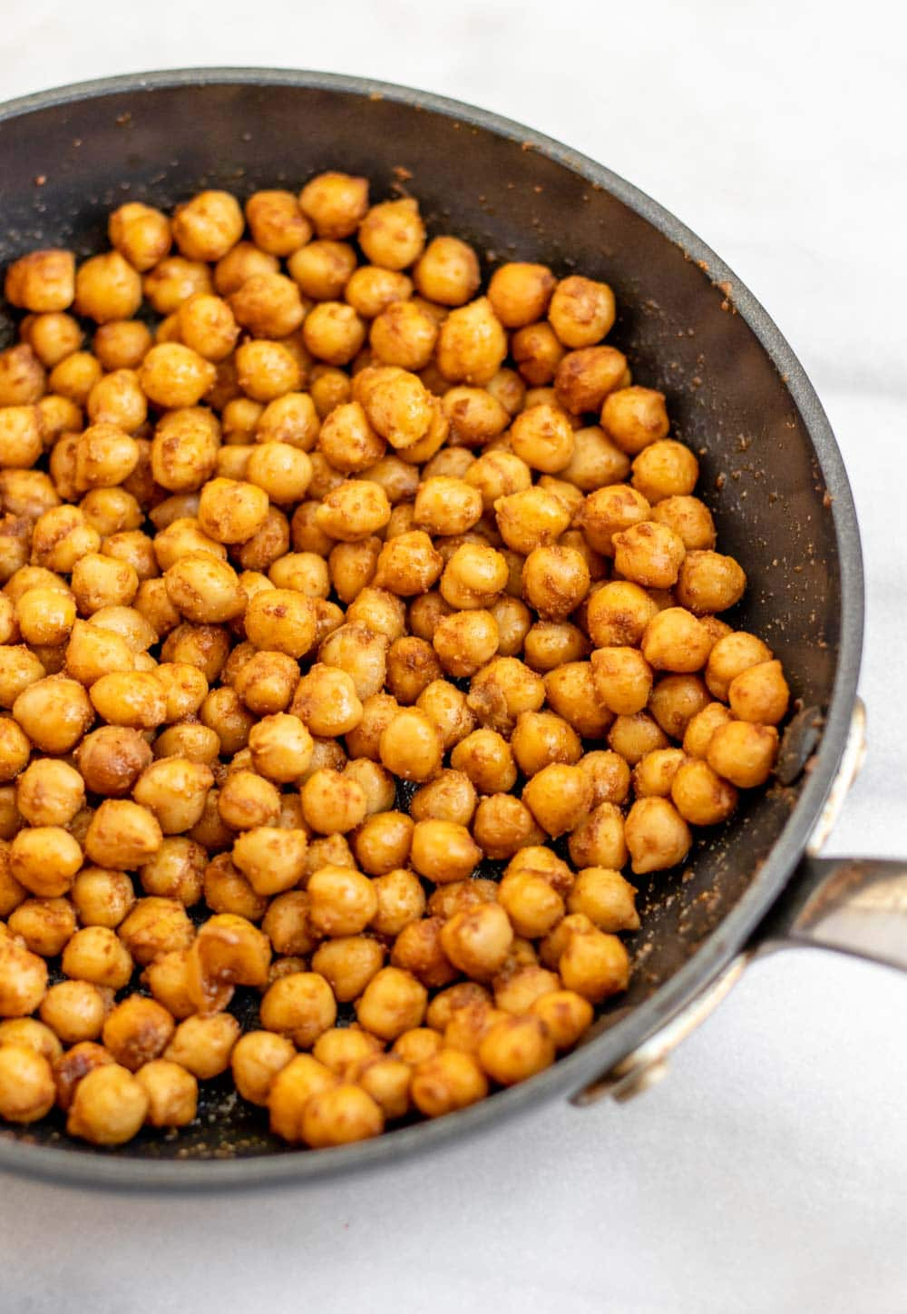 Sauteed chickpeas in a large pan with seasonings.