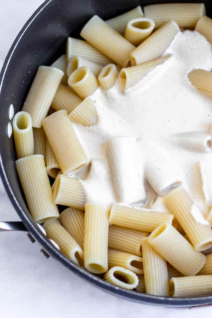 Cooked rigatoni with white cream sauce on top in the center.