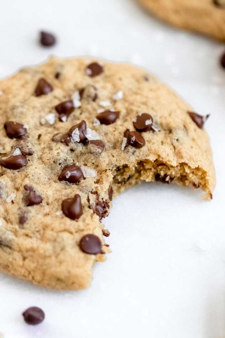 Up close of dairy free chocolate chip cookie showing a bite taken out.