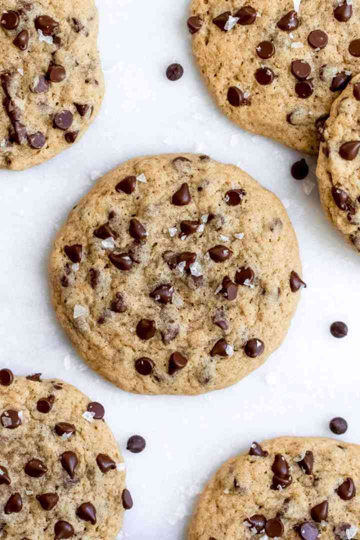 Up close of one dairy free cookie with mini chocolate chips and sea salt on top.
