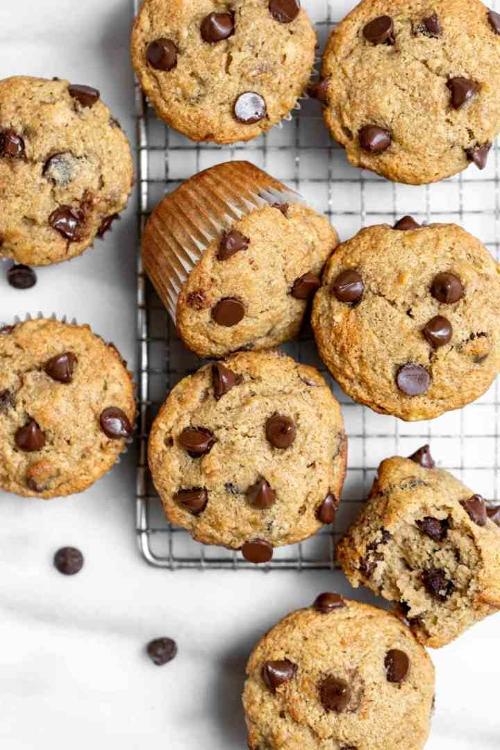 Gluten free banana muffins with chocolate chips on a marble backdrop.