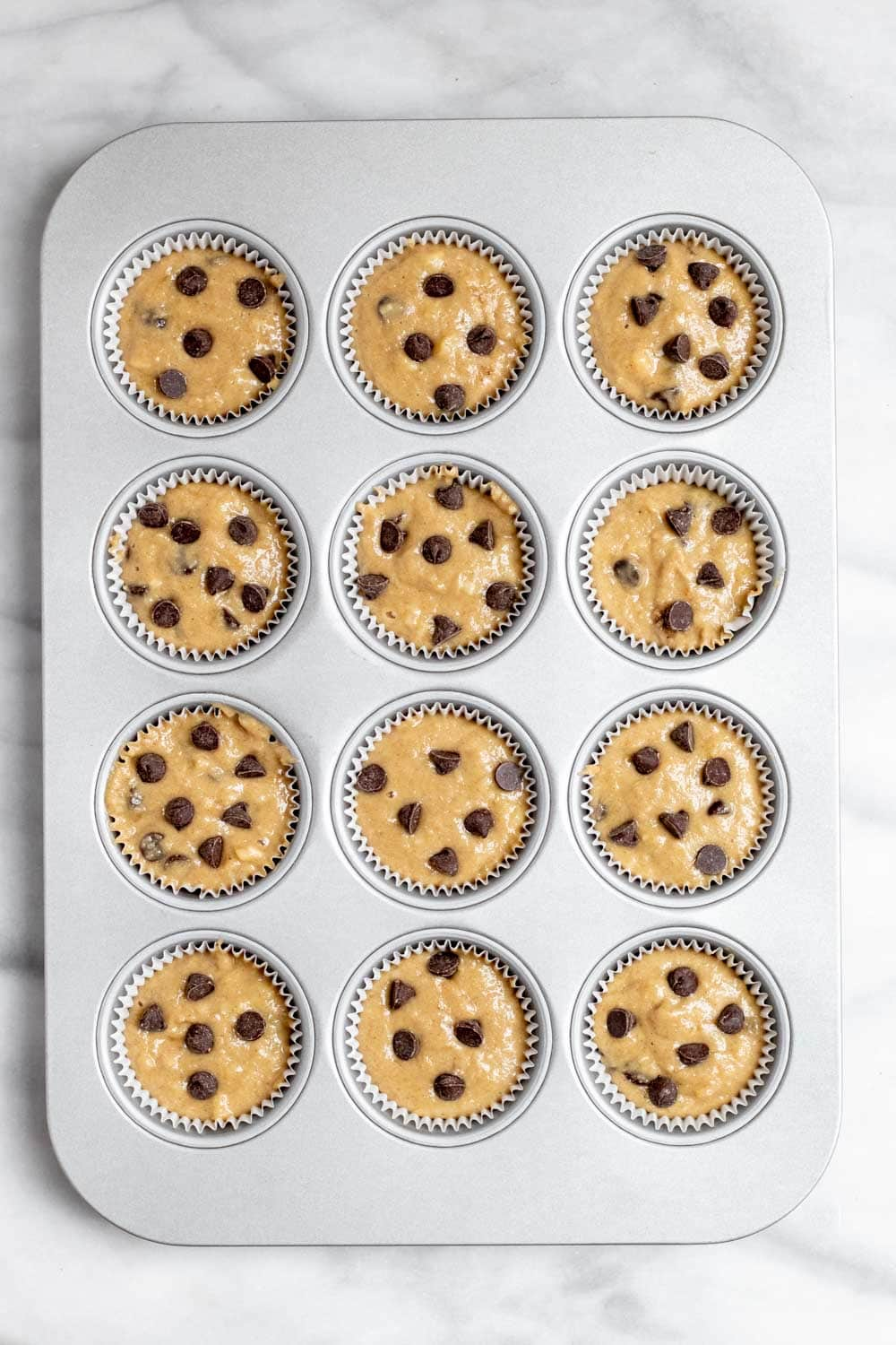 Muffins in a muffin tray before going in the oven.
