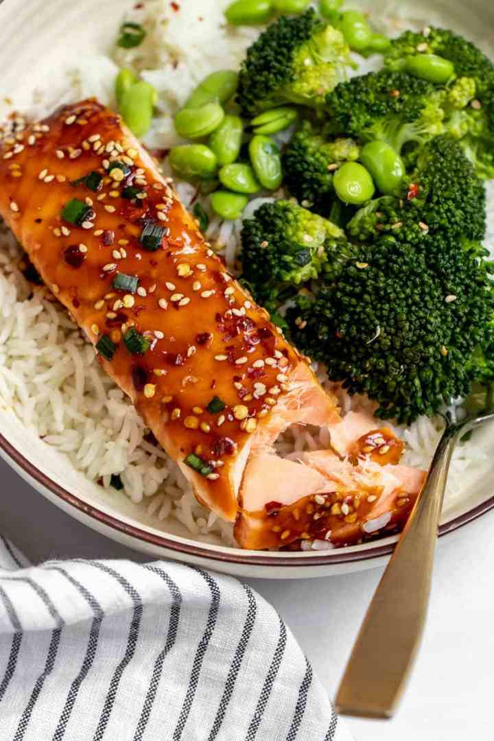 Baked teriyaki salmon over a bed of rice with one bite taken out.