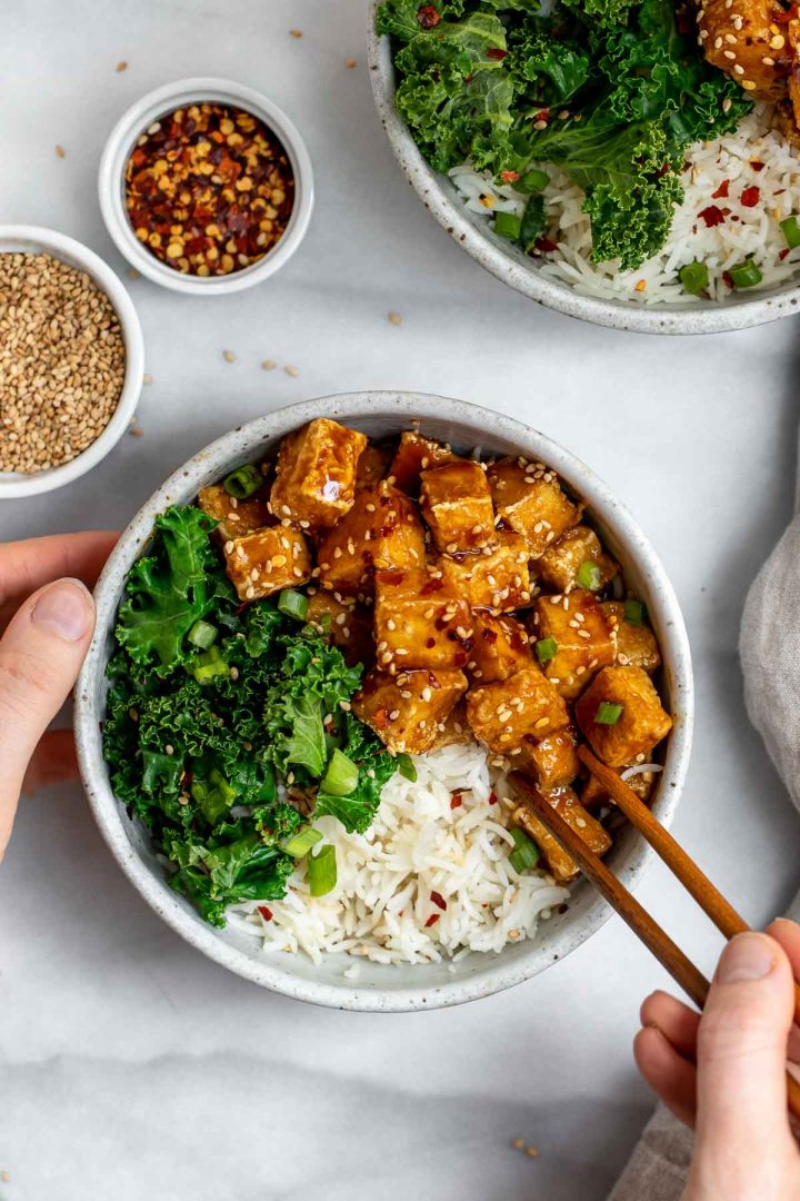 Hands holding a bowl with the tofu, kale and white rice.