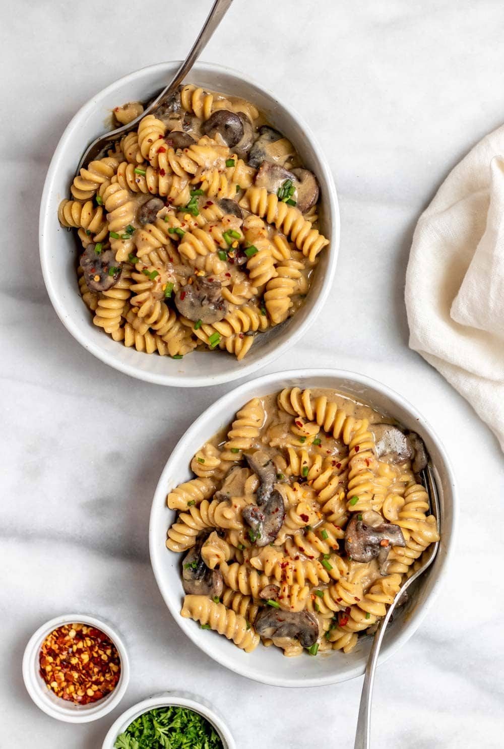 Two bowls with mushroom pasta and chives on top.