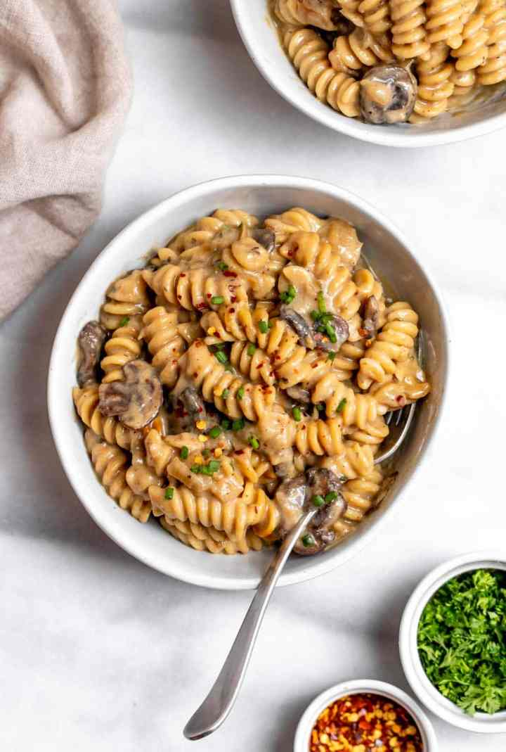 Vegan mushroom stroganoff in a bowl with a fork on the side.