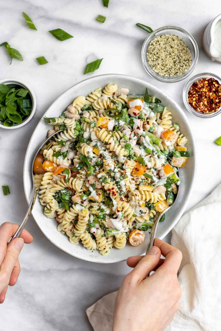 Vegan pasta salad with two spoons tossing everything together.