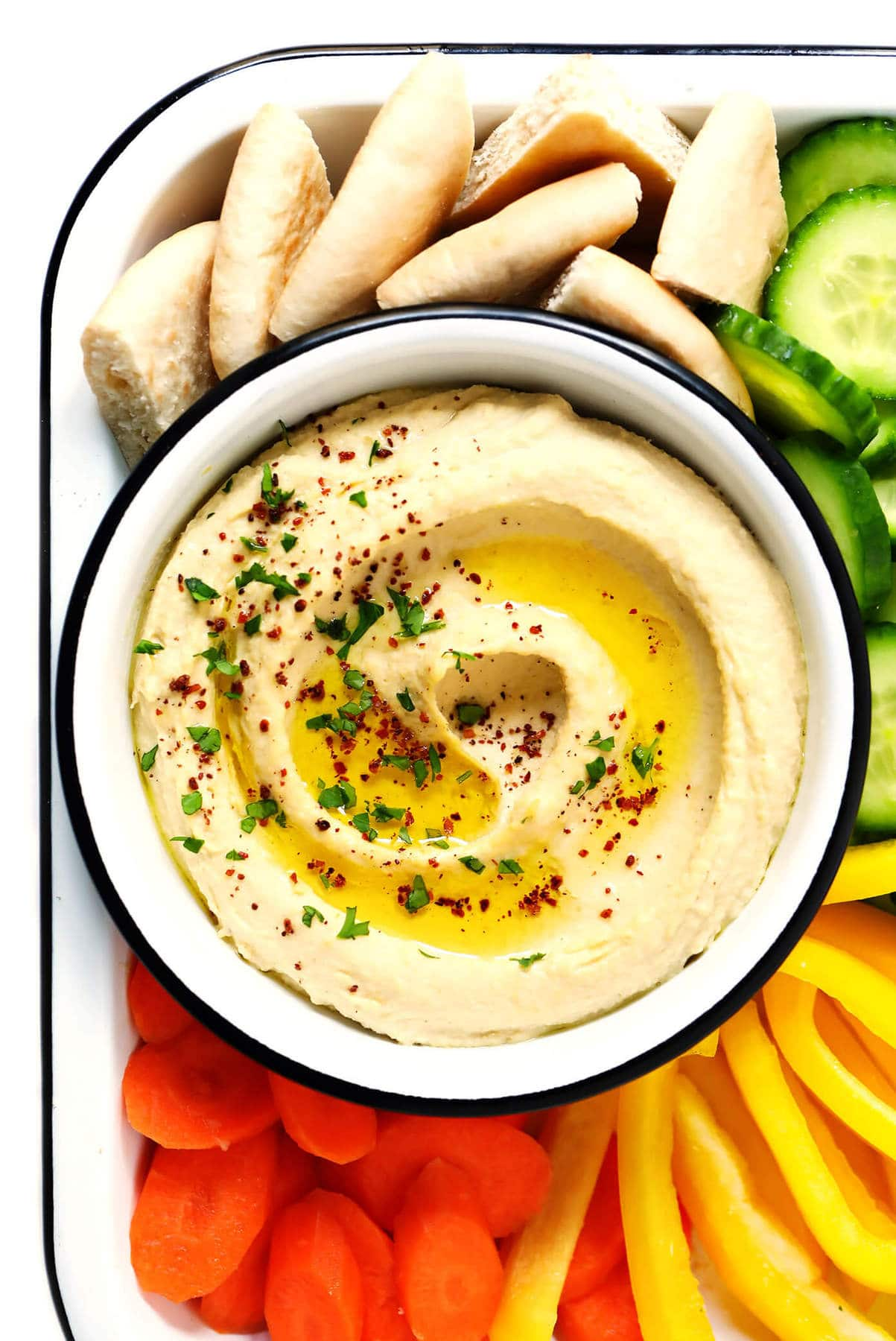Hummus in a small bowl with pita and veggies on the side.