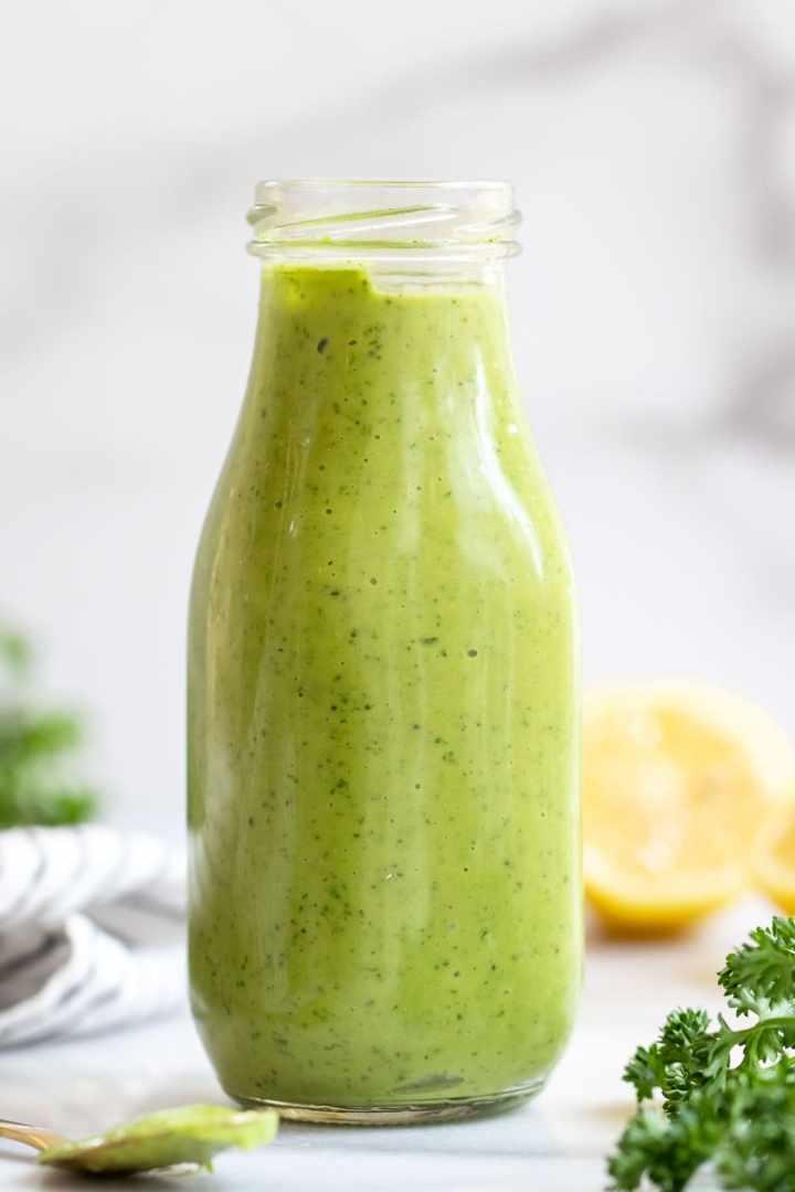 Glass bottle with vegan green goddess dressing on a white backdrop.
