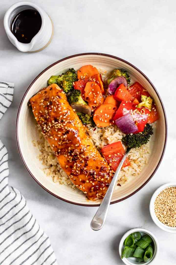 Maple soy glazed salmon on a bed of rice with roasted vegetables.